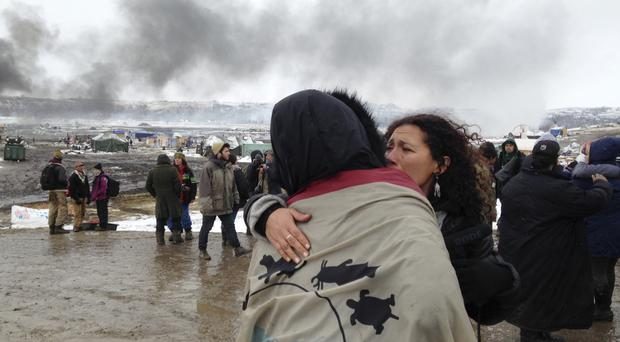 A couple embrace as opponents of the Dakota Access pipeline leave their main protest camp near Cannon Ball, North Dakota (James MacPherson/AP)