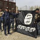 Iraq's federal police forces celebrate as they hold a flag of the Islamic State group they captured in Mosul (AP)