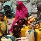 Displaced Somalis wait to fill plastic containers with water in a camp in the capital Mogadishu (Farah Abdi Warsameh/AP)