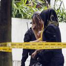 A female suspect, centre, is escorted to the Sepang court (AP)