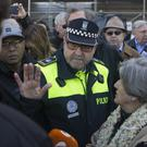 A police officer speaks to protesters from the Hazte Oir organisation outside the Town Hall in Madrid (Paul White/AP)