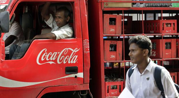 A man walks past a truck that distributes Coca Cola in Mumbai, India. (AP/Rajanish Kakade)