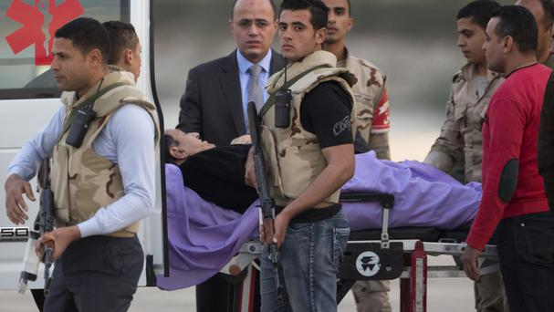 Hosni Mubarak is escorted into an ambulance at Maadi Military Hospital after an ambulance helicopter landed from the Cairo Police Academy-turned-court in Cairo (Amr Nabil/AP)