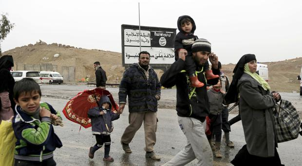 Families walk past an Islamic State sign while fleeing clashes between Iraqi forces and Islamic State group militants in western Mosul (AP)