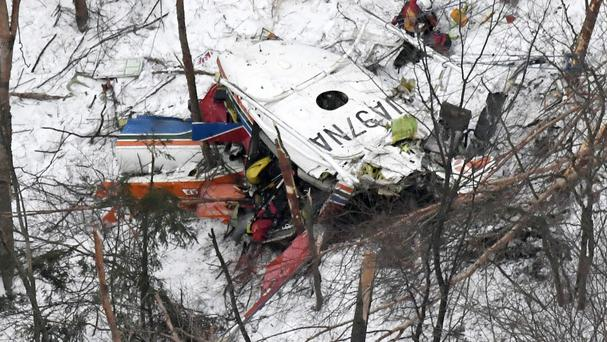 Rescuers work near the helicopter in mountains in Nagano prefecture (Kyodo News/AP)