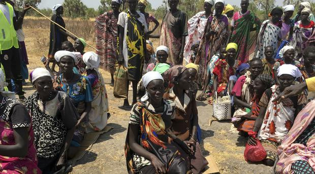 Women sit in line on the ground waiting to receive food distributed by the World Food Programme in Padeah, South Sudan (AP)