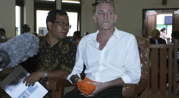 British national and former news correspondent David Fox listens to an Indonesian interpreter during his trial in Bali, Indonesia (Firdia Lisnawati/AP)
