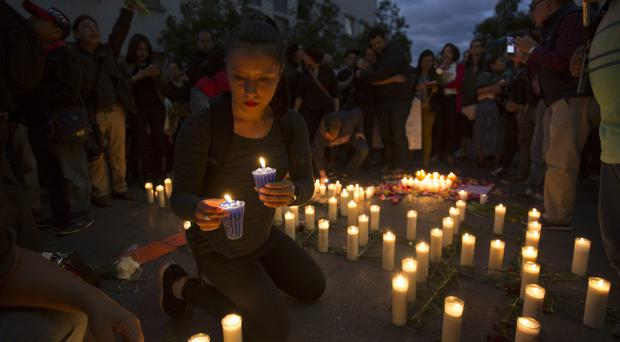 A woman lights a candle outside the presidential house during a protest to demand justice for the girls who died in a fire at the Virgin of the Assumption Safe Home in Guatemala City (Moises Castillo/AP)