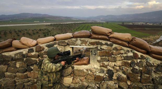 A Turkish army soldier holds his fighting position during exercises, at a military outpost near the town of Kilis, south-eastern Turkey, at the border with conflict-stricken Syria (AP)