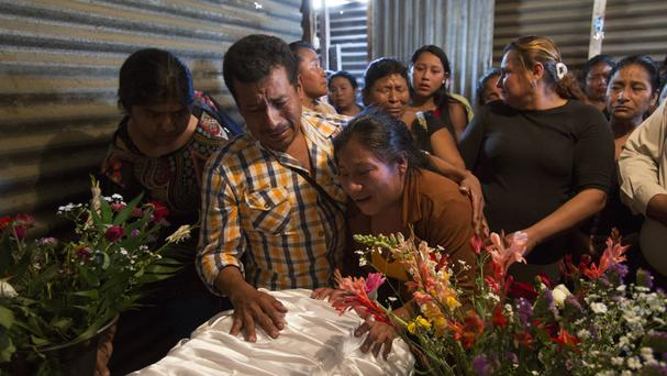 Marta Lidia Garcia, centre, cries during the wake for her 17-year-old daughter Siona Hernandez, who died in a youth shelter fire in Ciudad Peronia, Guatemala (Moises Castillo/AP)