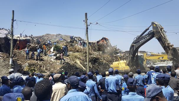 Police officers at the scene of the rubbish landslide as excavators aid rescue efforts