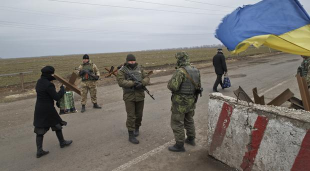 People cross a Ukrainian army checkpoint outside Kurakhove, Ukraine, just a few miles away from the area controlled by Russia-backed rebels (AP)