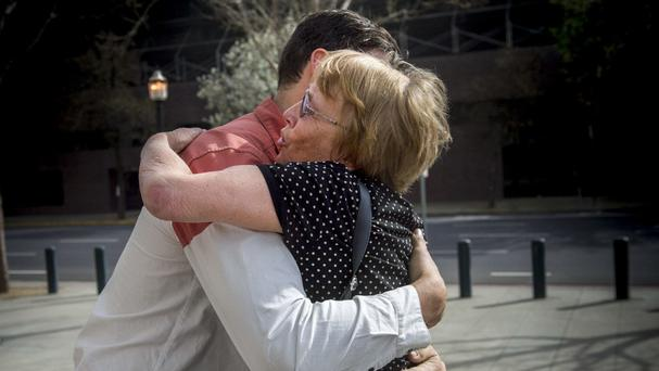 Marianne Quinn the mother of Aaron Quinn, one of Matthew Muller's victims, hugs one of her son's friends (Hector Amezcua/The Sacramento Bee via AP)