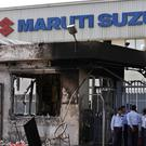 Security guards stand near a burnt-down reception block at the Maruti Suzuki factory in Manesar (Saurabh Das/AP)