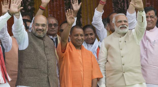 Indian Prime Minister Narendra Modi, front right, Yogi Adityanath, centre in saffron robes, and Bharatiya Janata Party president Amit Shah (Rajesh Kumar Singh/AP)