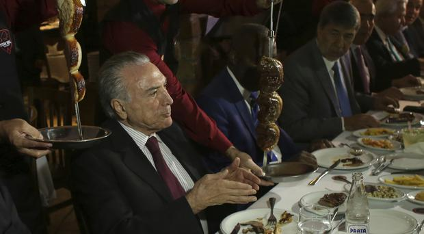 President Michel Temer of Brazil hosts a dinner for diplomats at a traditional barbecue restaurant (AP Photo/Eraldo Peres)