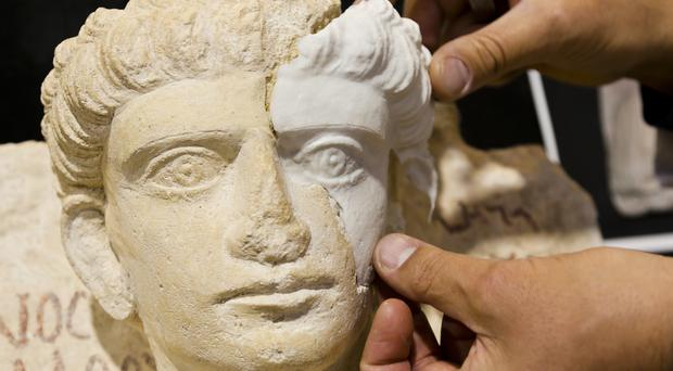 Restorer Antonio Iaccarino Idelson shows a computer-rendered, 3D print-generated replica of a missing part of a limestone male bust, dated between the 2nd and the 3rd century AD which was damaged during the Islamic State occupation of the Syrian city of Palmyra (AP)