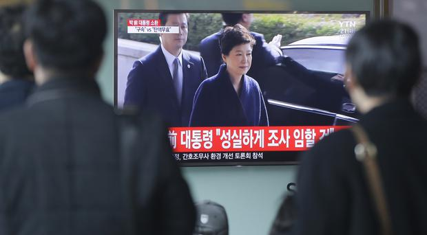People at Seoul railway station watch a TV news programme showing ousted president Park Geun-hye arriving at the prosecutors office (AP)