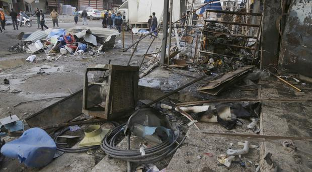 People inspect the aftermath of a suicide car bombing in a commercial area in Baghdad's south-western Amil neighbourhood (AP)