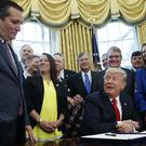 President Donald Trump jokes during a signing ceremony in the Oval Office to increase Nasa's budget (Evan Vucci/AP)