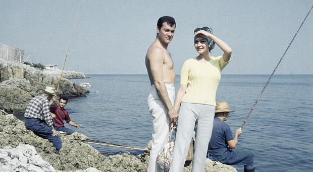 American actor Tony Curtis poses with his wife, Christine Kaufmann, who has died aged 72, in Cannes, France, in 1965 (AP)