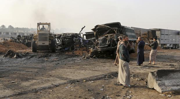 Civilians inspect the aftermath of a deadly suicide bombing in southern Baghdad (Karim Kadim/AP)