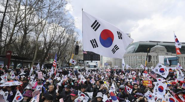 Supporters of former president Park Geun-hye hold national flags during a rally in Seoul, South Korea (AP)
