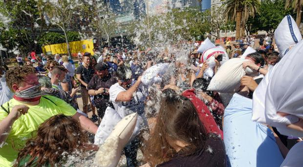 Feathers fly as participants take part in a giant pillow fight in Pershing Square, Los Angeles (AP)