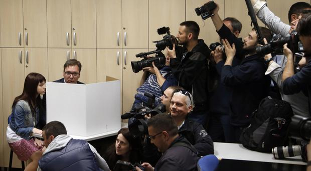 Serbian Prime Minister and presidential candidate Aleksandar Vucic (left) prepares his ballot with daughter Milica at a polling station in Belgrade (Darko Vojinovic/PA)