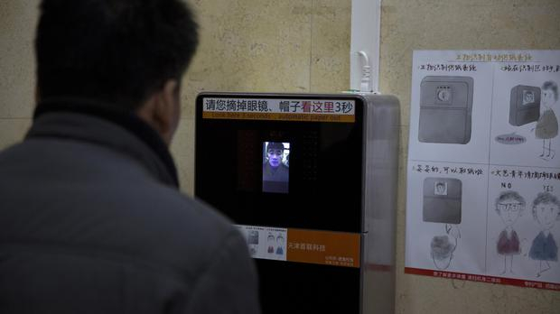 A man tries out a facial recognition toilet paper dispenser in the Temple of Heaven park in Beijing (AP)