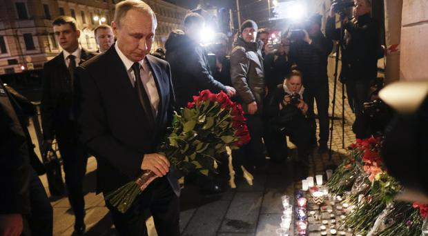 Russian president Vladimir Putin lays flowers near the Technological Institute station in St.Petersburg (AP)