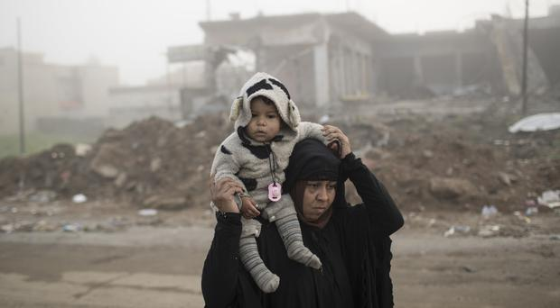 A woman carries her daughter as they flee fighting between Iraqi security forces and Islamic State militants on the western side of Mosul (AP/Felipe Dana)