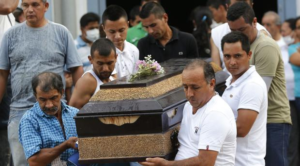 Men carry the coffin of a relative during a mass funeral in Mocoa, Colombia (AP/Fernando Vergara)