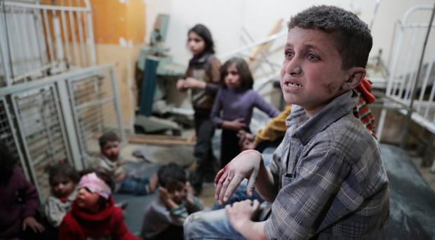 Syrian children wait to receive treatment at a makeshift clinic in Douma, following reports of air strikes