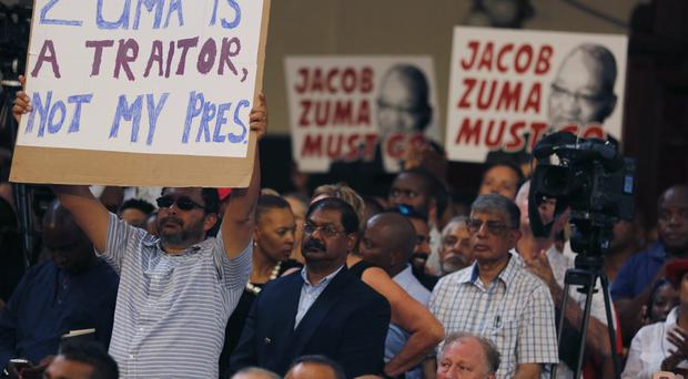 Protesters raise placards against South African President Jacob Zuma (AP/Denis Farrell)