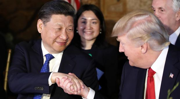 Donald Trump and Chinese president Xi Jinping shake hands during their dinner at Mr Trump's Mar-a-Lago resort in Florida (AP)