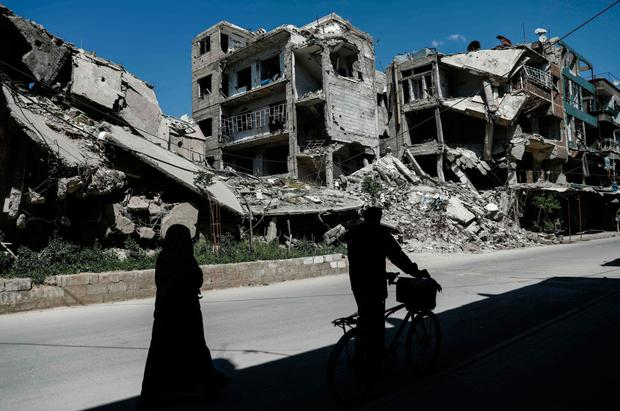 Syrians walk past damaged buildings on in the rebel-held town of Douma, on the eastern outskirts of Damascus