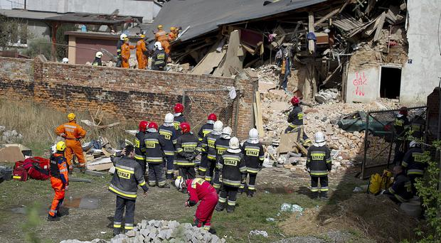 Rescuers and firefighters search for missing people in the rubble of an apartment building that collapsed in Swiebodzice, Poland (AP)