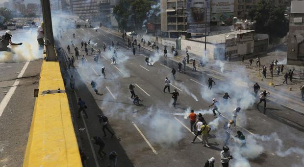 Demonstrators hurl back tear gas canisters shot by riot police during a protest in Caracas (AP)