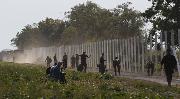 Hungarian soldiers work on a fence that is being built at the border with Croatia (AP)