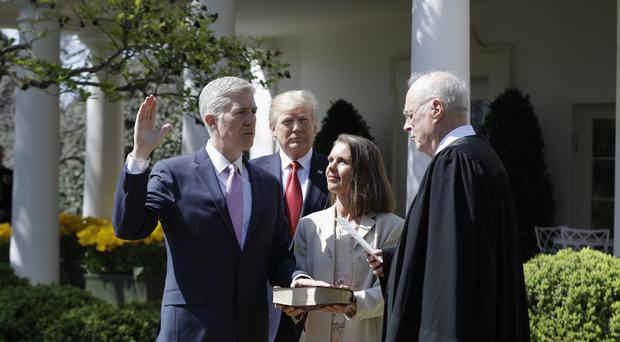 President Donald Trump watches as Supreme Court Justice Anthony Kennedy administers the judicial oath to Neil Gorsuch in the Rose Garden of the White House (AP)