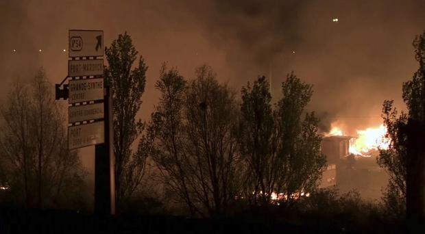 In an image made from video, flames and smoke are seen at a migrant camp near Dunkirk (AP Photo)