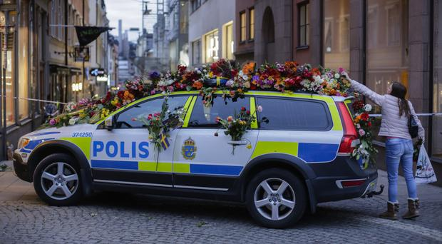 A woman drops flowers onto a police car in central Stockholm, Sweden (AP/Markus Schreiber)
