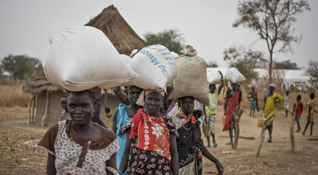 People walk back to their homes after receiving food distributed in South Sudan (AP)