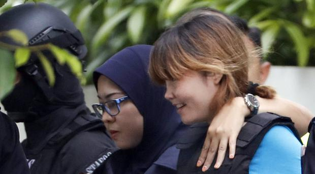 Vietnamese suspect Doan Thi Huong, right, is escorted by police officers as she leaves court in Sepang, Malaysia (AP Photo/Vincent Thian)
