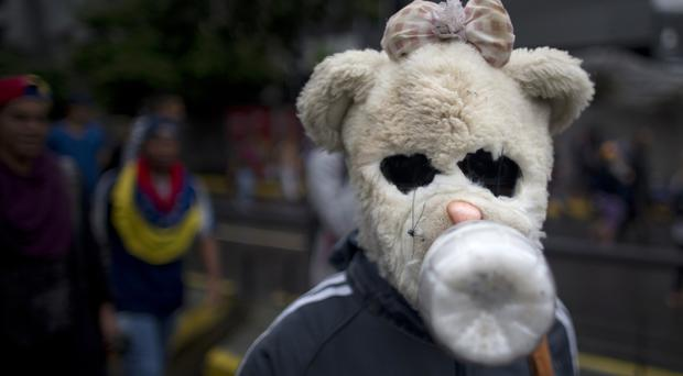 A demonstrator wearing a makeshift gas mask fashioned with the head of a teddy bear takes part in an anti-government protest in Caracas (AP Photo/Ariana Cubillos)
