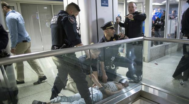 Police detain a man who became belligerent and sparked a stampede among passengers at an overcrowded railway station in New York (AP Photo/Mary Altaffer)