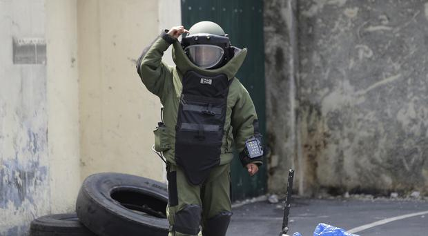 A member of the bomb squad gestures after checking a bag suspected to contain a bomb during an anti-terror simulation exercise at a bus terminal in Quezon city (AP)