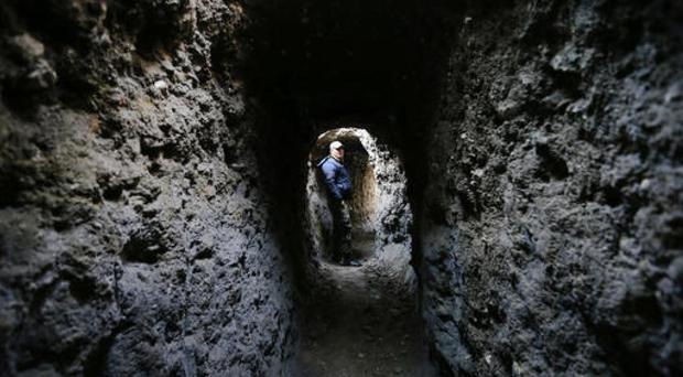 A Syrian army soldier makes his way in a tunnel reportedly previously used by rebel fighters (AP)