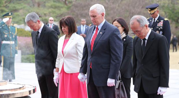 US vice president Mike Pence, second from right, pays a silent tribute with his wife Karen at the Seoul National Cemetery in the South Korean capital